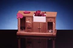 Detalle de los muebles retros de la cocina de la casa de muñecas, armario con el fregadero en fondo negro y azul imagen de archivo