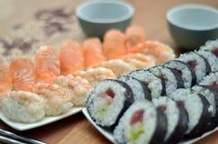 Detalle de los rollos de sushi del maki y del sushi del nigiri con la comida de Japón de los salmones y del camarón en la tabla Imagen de archivo libre de regalías