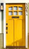Detalle de madera amarillo de la puerta en un edificio de piedra Imágenes de archivo libres de regalías