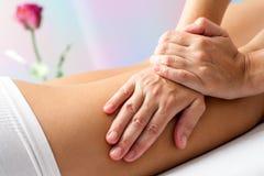 Detalle de manos que da masajes a los tendones de la corva de la hembra Foto de archivo
