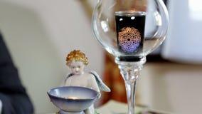 Detalle de poca estatua y una vela en un vidrio almacen de metraje de vídeo