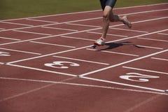 Detalle de un atleta de sexo masculino en una pista corriente Imagenes de archivo