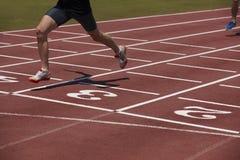 Detalle de un atleta de sexo masculino en una pista corriente Imagen de archivo libre de regalías