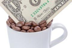Detalle de un billete de banco del dólar de EE. UU. en una taza de granos de café en whi Imágenes de archivo libres de regalías