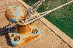 Detalle de un bitt con las cadenas y las cuerdas para amarrar en el puerto Imagen de archivo libre de regalías