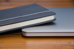 Detalle de un cuaderno y de un ordenador portátil en la tabla de madera Fotos de archivo libres de regalías