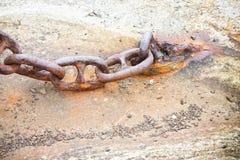 Detalle de una cadena oxidada vieja del metal anclada a un bloque de cemento Fotos de archivo libres de regalías