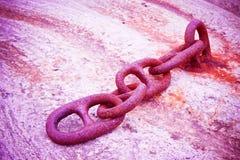 Detalle de una cadena oxidada vieja del metal anclada a un bloque de cemento Imagen de archivo