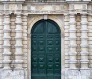 Detalle de una fachada urbana vieja de la piedra de construcción con la puerta de madera verde alta y las columnas decorativas fotografía de archivo