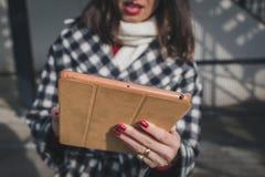 Detalle de una mujer joven que usa su tableta en las calles de la ciudad Imágenes de archivo libres de regalías