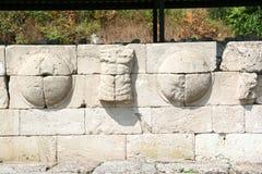Detalle de una pared de escudos y de torsos a lo largo de la carretera principal Dion Fotografía de archivo