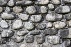 Detalle de una pared hecha de piedras del río, de colores de fondo oscuros de piedra, de la pared, del pavimento, grises y marron Foto de archivo