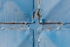 Detalle de una puerta azul de la chapa con los remaches Fotos de archivo