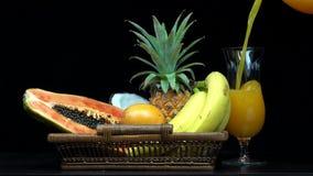Detalle de verter el zumo de naranja en un vidrio, frutas exóticas en una cesta metrajes