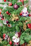 Detalle del árbol verde de la Navidad (Chrismas) con los ornamentos coloreados, globos, estrellas, Santa Claus, muñeco de nieve Fotos de archivo