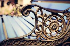 Detalle del banco de parque viejo con los ornamentos, fondo del bokeh Imágenes de archivo libres de regalías