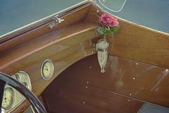 Detalle del barco de madera de la velocidad del vintage con el florero cristalino en tenedor del florero con una rosa roja en el  fotos de archivo libres de regalías