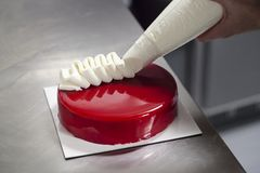 Detalle del bolso de los pasteles que adorna una torta de la cereza foto de archivo