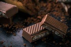 Detalle del chocolate con el relleno cremoso en tablero negro con cacao Foto de archivo libre de regalías