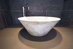 Detalle del cuarto de baño con el lavabo de colada de mármol redondo imagen de archivo