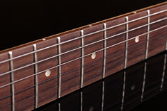 Detalle del fretboard de una guitarra, en un fondo oscuro Fotos de archivo