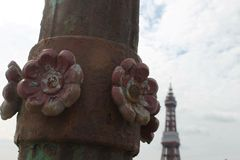 Detalle del hierro de la rosa del rojo de Lancashire en posts de la lámpara en el embarcadero del norte Blackpool con la torre de Fotos de archivo libres de regalías