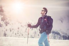 Detalle del hombre del esquiador con las gafas de sol tierra nevosa de exploración que camina y que esquía con el esquí alpino Mo imagenes de archivo