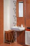 Detalle del interior moderno del cuarto de baño privado en naranja con floral Foto de archivo