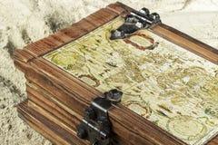 Detalle del pecho de madera con un portolan en su cubierta, en la arena de la playa Imágenes de archivo libres de regalías