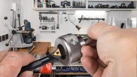 Detalle del pedazo de la herramienta y perno metálico en manos del ` s del trabajador fotografía de archivo
