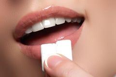 Detalle del primer de la mujer que pone el chicle rosado en su boca Imagen de archivo