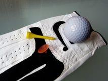 Detalle del primer de la pelota de golf del guante de golf y de la camiseta amarilla fotos de archivo