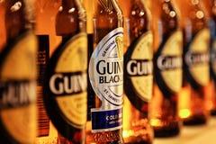 Detalle del primer de las botellas de Guinness en fila Imagen de archivo
