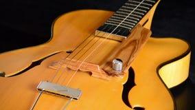 Detalle del puente, de la secuencia, de trastes y de f de un rotatint de la guitarra eléctrica del jazz en fondo negro almacen de metraje de vídeo