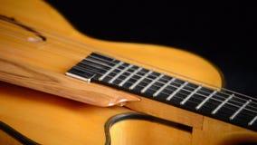 Detalle del puente, de secuencias y de efes de una guitarra eléctrica del jazz que gira en el fondo negro metrajes