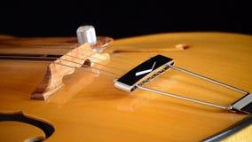 Detalle del puente, de secuencias y de efes de una guitarra eléctrica del jazz que gira en el fondo negro almacen de metraje de vídeo