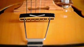 Detalle del puente, de secuencias y de efes de una guitarra eléctrica del jazz que gira en el fondo negro almacen de video