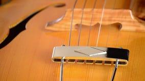 Detalle del puente, de secuencias y del efe del cuerpo de una guitarra eléctrica clásica del jazz que gira en fondo negro almacen de video