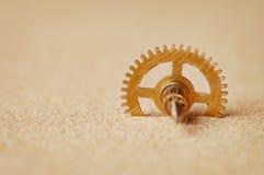 Detalle del reloj - un engranaje en la arena Imágenes de archivo libres de regalías