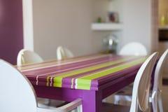 Detalle del sitio dinning con la tabla y las sillas coloridas Foto de archivo libre de regalías