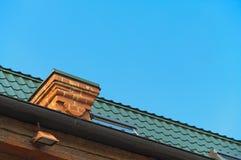 Detalle del tejado con las chimeneas contra el cielo azul fotografía de archivo