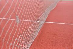 Detalle del tenis neto en el campo hecho de rubbe rojo del gránulo selec Fotografía de archivo libre de regalías