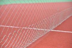 Detalle del tenis neto en el campo hecho de rubbe rojo del gránulo selec Imagen de archivo