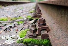 Detalle del tornillo del carril en la vía abandonded del tren Imágenes de archivo libres de regalías