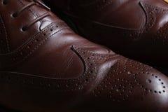 Detalle delantero de un par de zapatos clásicos de cuero marrones de la abarca con el cordón Foto de archivo