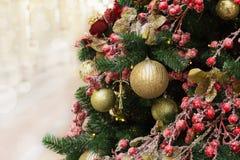 Detalle el árbol de navidad con el día de fiesta rojo, bolas de oro con el espacio de la copia en fondo borroso del bokeh en inte Fotografía de archivo