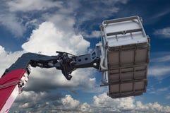 Detalle hidráulico del brazo y de la cesta de la grúa en fondo del cielo Imagen de archivo