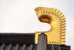 Detalle japonés del tejado del templo - adorno de oro del final en el embaldosado del tejado fotos de archivo
