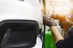 Detalle la imagen de las manos del mecánico con la herramienta, cambiando el neumático del coche imagen de archivo libre de regalías