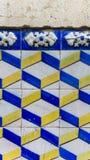 Detalle las tejas de los azulejos azules y amarillas con la pared de piedra Imagen de archivo libre de regalías